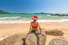 Santa Claus in tropical beach. Beautiful, fashionable woman with red Santa Claus hat relaxing and catching tan on rocks of a tropical beach for xmas holiday in Royalty Free Stock Images