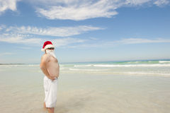 Santa Claus tropical beach holiday. Happy joyful and cheerful Santa Claus on summer holiday, standing in shallow water at tropical beach, with ocean and blue sky stock photo