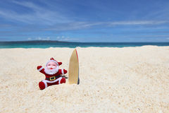 Santa Claus at tropical beach. Santa Claus surfer on sand at tropical ocean beach, Christmas and New Year winter vacation concept Royalty Free Stock Photos