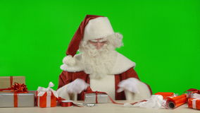 Santa Claus is Trying to Wrap a Gift stock video