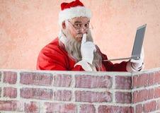 Santa Claus trzyma laptop z palcem na wargach Obrazy Royalty Free
