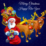 Santa Claus and two deers with cart full of gifts Royalty Free Stock Photo