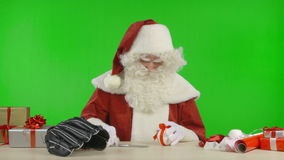 Santa Claus is Tying a Bow on a Baseball stock video