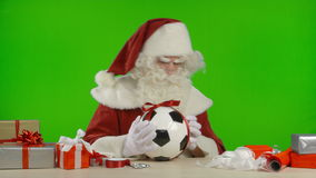 Santa Claus is Tying a Bow on a Soccer Ball stock video