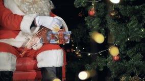 Santa Claus tying ribbons on a gift box. Christmas Eve concept. Santa Claus tying ribbons on a gift box during Christmas Eve. 4K stock video