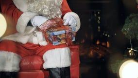 Santa Claus tying ribbons on a gift box. Christmas Eve concept. Santa Claus tying ribbons on a gift box during Christmas Eve. 4K stock video footage