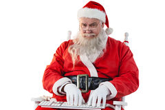 Santa claus typing keyboard against white background Stock Image