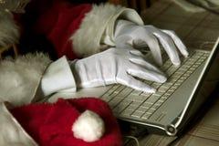Santa Claus typing on laptop Royalty Free Stock Photos