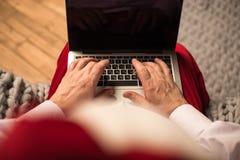 Santa Claus typing on laptop. Hands of Santa Claus typing on laptop Stock Photography