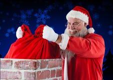 Santa Claus umieszcza jego prezenta worek w komin Fotografia Stock