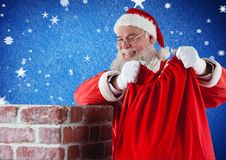 Santa Claus umieszcza jego prezenta worek w komin Zdjęcia Stock