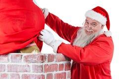 Santa Claus umieszcza prezenta pudełko w komin Obrazy Royalty Free