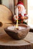 Santa Claus und eine Kerze in einer Kokosnuss Lizenzfreies Stockfoto