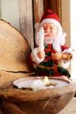 Santa Claus und eine Kerze in einer Kokosnuss Lizenzfreie Stockfotografie