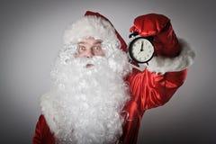 Santa Claus und eine Uhr Lizenzfreie Stockbilder