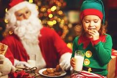 Santa Claus- und Elfenkind in Weihnachtstrinkmilch und -c$essen lizenzfreie stockbilder