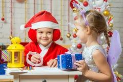 Santa Claus- und Feenspaß, zum des jeder des anderen Assistenten zu betrachten, der Grußkarten und -geschenke vorbereitet Stockbild