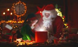 Santa Claus und kleine Elfe mit magischem Geschenk für Weihnachten Lizenzfreie Stockbilder