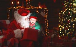 Santa Claus und kleine Elfe mit magischem Geschenk für Weihnachten Lizenzfreies Stockbild