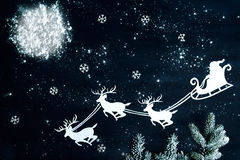 Santa Claus- und Renfliegen durch den nächtlichen Himmel Stockbild