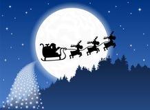Santa Claus und sein Renpferdeschlitten hintergrundbeleuchtet durch Stockfotografie