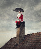 Santa Claus under the rain. Sheltering himself with an umbrella Stock Images
