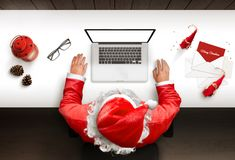 Santa Claus uses a laptop with isolated, blank screen for mockup, web site presentation stock photography