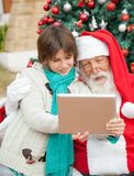 Santa Claus Using Digital Tablet With Boy Royalty Free Stock Image