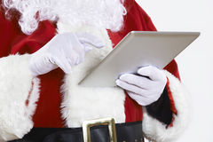 Santa Claus Using Digital Tablet On White Background Royalty Free Stock Photos
