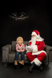 Santa Claus using hexacopter drone with child. On dark background stock images