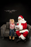 Santa Claus using hexacopter drone with child. Sitting on grey chair royalty free stock images