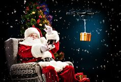 Santa Claus using hexacopter drone. With giftbox stock image