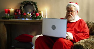 Santa claus using laptop. During christmas time at home 4k stock video footage