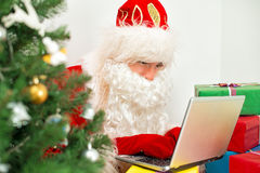 Santa Claus is using laptop. Stock Images
