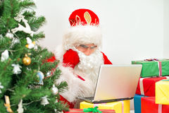 Santa Claus is using laptop. Royalty Free Stock Photography
