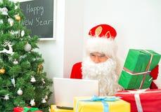 Santa Claus is using laptop. Royalty Free Stock Photo