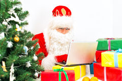 Santa Claus is using laptop. Royalty Free Stock Image