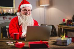 Santa Claus using laptop on table. At home royalty free stock photos