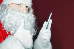 Santa Claus using a mobile phone at Christmas time Stock Photos