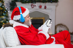 Santa claus using mobile phone at home. During christmas time Royalty Free Stock Images