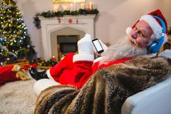 Santa claus using mobile phone at home Stock Images