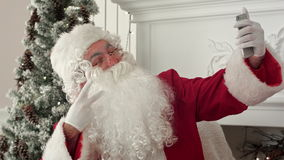 Santa Claus using mobile phone to take Xmas selfies. Professional shot on BMCC RAW with high dynamic range. You can use it e.g. in your commercial video stock video