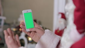 Santa Claus Using Phone With Green Screen in Home. Smartphone with Green Screen in Vertical Mode. Easy for tracking and keying. ProRes HQ codec stock footage