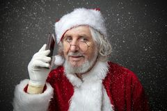 Santa Claus using smartphone - calling phone or texting a message Royalty Free Stock Photos