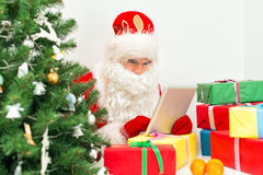Santa Claus is using tablet pc. Royalty Free Stock Photography