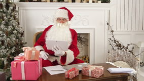 Santa Claus using tablet to give a quick video call to the North Pole stock footage