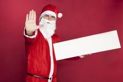 Santa Claus utför en stoppgest som annonserar i hans hand royaltyfri bild