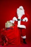 Santa Claus vem com um saco grande dos presentes Retrato cheio do comprimento Imagens de Stock