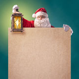 Santa Claus with vintage lantern and a poster Stock Photography