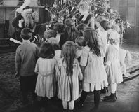 Santa Claus visiting with large group of children Stock Images
